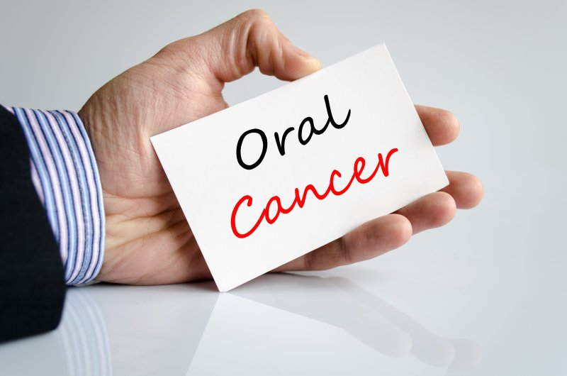 "A man holding a white card that has ""Oral Cancer"" written on it"