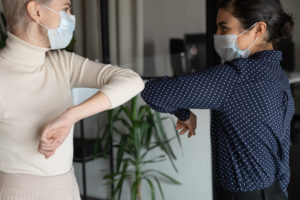 Two women wearing face masks and bumping elbows